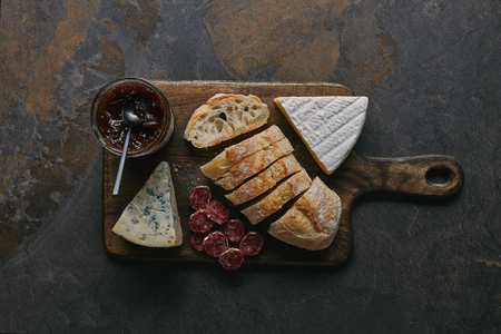 top view of sliced bread, delicious cheese, salami and jam on wooden cutting board