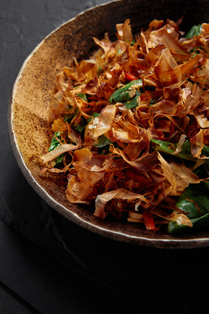 close-up view of plate with delicious traditional japanese dish with katsuobushi, dried bonito shavings