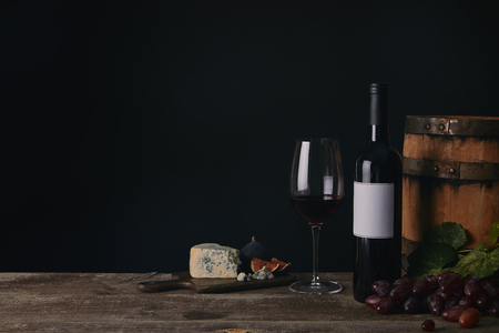close-up view of glass, bottle and barrel of wine with cheese and grapes on black Standard-Bild