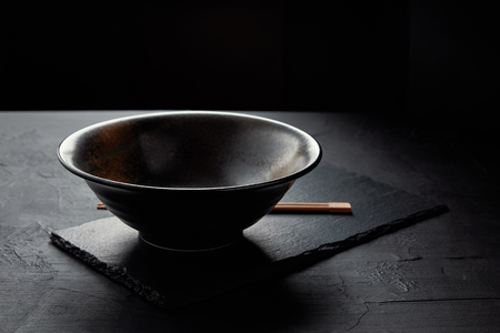 close-up view of empty bowl and chopsticks on black slate board