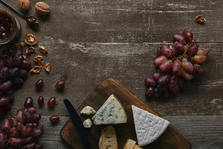 top view of fresh ripe grapes, walnuts, cheese and delicious jam on wooden table Stok Fotoğraf