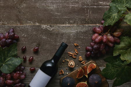 top view of wine bottle with blank label, fresh grapes, figs and nuts on wooden table