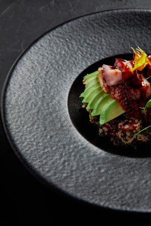 close-up view of delicious traditional japanese dish with seafood, avocado and herbs on black plate Stock Photo