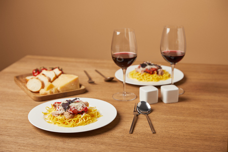 plates of tasty pasta with red wine in glasses on wooden table 写真素材