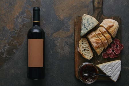 top view of wine bottle with blank label, sliced bread, salami and cheese on wooden cutting board