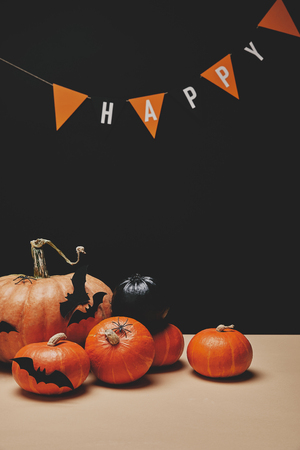 pumpkins, paper bats and paper garland with word happy, halloween concept