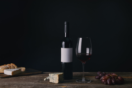 bottle of wine with blank label, glass of red wine, cheese and grapes on wooden table Stock fotó