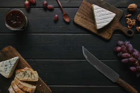 top view of knife, delicious jam and gourmet snacks on wooden table
