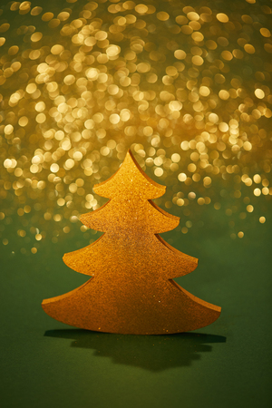 golden glittering christmas tree for decoration on green background Фото со стока