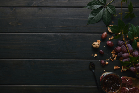top view of fresh ripe grapes, walnuts, green leaves, jam and sliced salami on wooden table