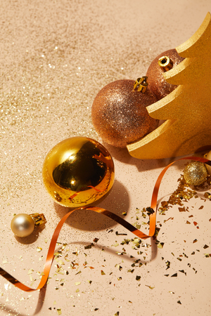 high angle view of christmas balls, decorative christmas tree, wavy ribbon and glitter on tabletop