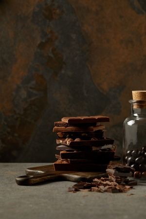 delicious assorted chocolate pieces on chopping board and gourmet chocolate balls in glass jar Banco de Imagens