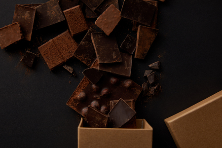 top view of box and assorted delicious chocolate pieces on black 스톡 콘텐츠