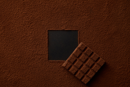 gourmet cocoa powder with square copy space and chocolate on black background