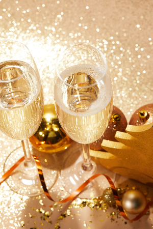 high angle view of christmas balls and two glasses of champagne with glitter on tabletop