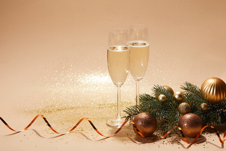 glittering christmas balls, pine branch and glasses of champagne on tabletop