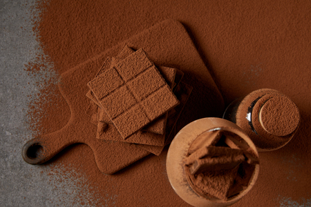 top view of tasty chocolate pieces with cocoa powder on chopping board 版權商用圖片