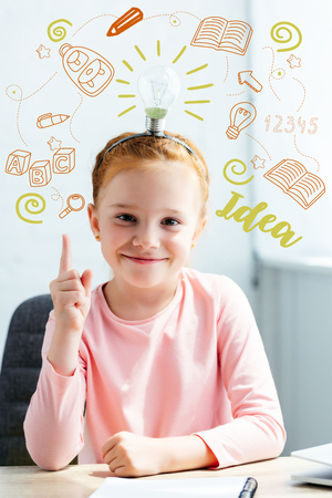 beautiful schoolgirl pointing up on light bulb on head with idea and icons