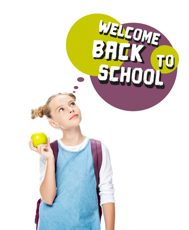 schoolchild holding apple and looking up at speech bubble with welcome back to school lettering, isolated on white