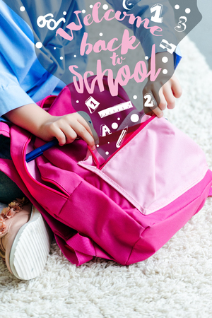 cropped shot of child packing pink school bag at home, welcome back to school Stock Photo