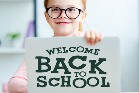 Adorable red haired schoolgirl in eyeglasses using laptop with welcome back to school lettering