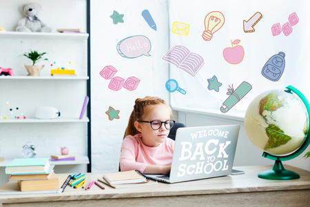 beautiful child in eyeglasses using laptop while studying at desk at home, welcome back to school Фото со стока