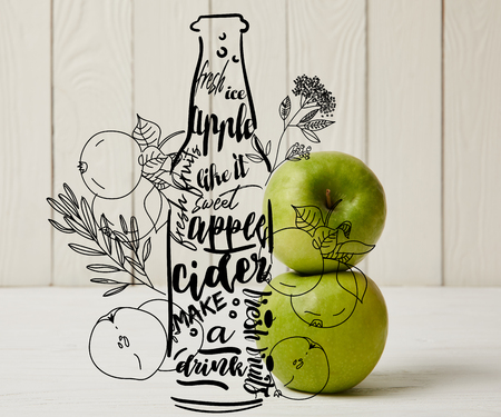 Fresh green apples on wooden background with illustration of cider bottle