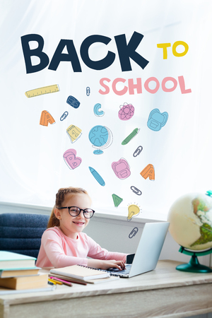 Adorable kid in eyeglasses smiling at camera while studying with laptop at home with icons and back to school lettering