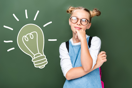 pensive schoolchild in glasses looking up near blackboard with light bulb sign Imagens