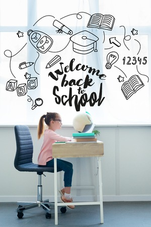 Side view of little schoolgirl studying with books and laptop at home, with icons welcome back to school lettering Фото со стока