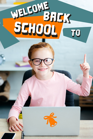 Adorable red haired schoolgirl in eyeglasses pointing up with finger and smiling at camera while using laptop at home with welcome back to school lettering