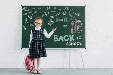 adorable little schoolgirl with backpack showing blackboard with icons and back to school lettering 写真素材
