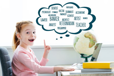 cheerful redhead child studying with books and laptop and pointing up on words of different professions in speech bubble