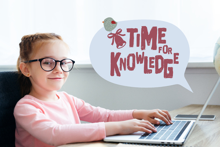 Beautiful kid in eyeglasses using laptop with time for knowledge lettering in speech bubble
