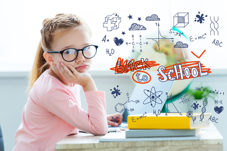 Bored child in eyeglasses looking at camera while studying with laptop and books with back to school lettering and icons Stock Photo