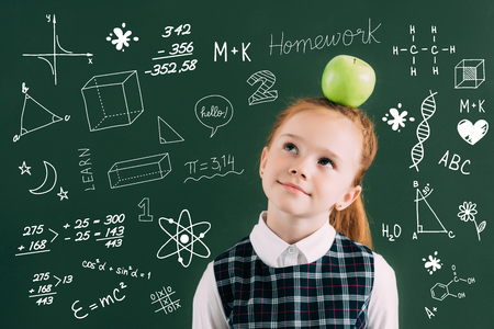 pensive little red haired schoolgirl with apple on head standing near chalkboard with school icons Stock Photo