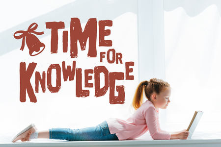 adorable little schoolgirl reading book and lying on windowsill with time for knowledge lettering