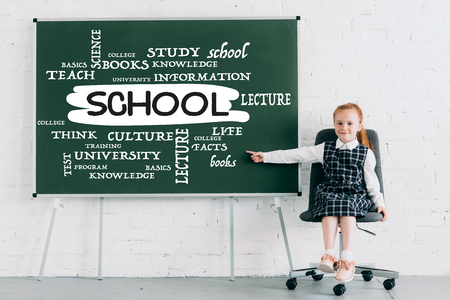 adorable little schoolgirl smiling at camera and pointing at chalkboard with school word 版權商用圖片 - 108754931