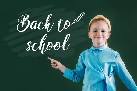 beautiful red haired schoolgirl pointing at chalkboard with back to school lettering 스톡 콘텐츠