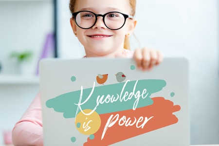 red haired schoolgirl in eyeglasses using laptop with knowledge is power lettering
