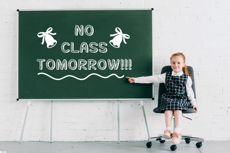 adorable little schoolgirl smiling at camera and pointing at chalkboard with no class tomorrow lettering