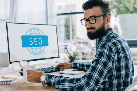 young successful seo manager sitting at workplace with computer and looking at camera Stock fotó - 108755064