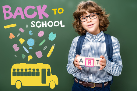 schoolboy holding wooden cubes with word art near blackboard, with icons, bus and