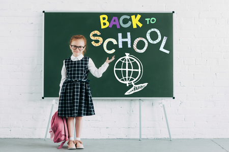 adorable little schoolgirl with backpack showing blackboard with back to school lettering