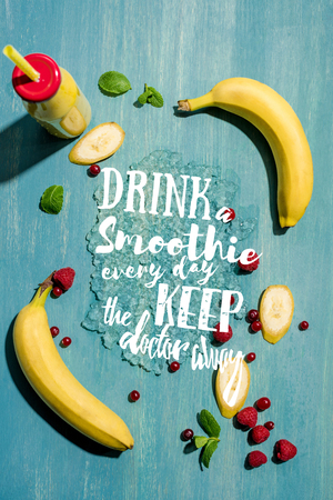 top view of bottle with fresh banana smoothie and berries with mint leaves, with drink smoothie every day keep the doctor away lettering