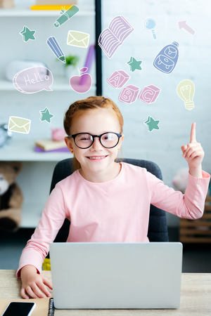 Adorable red haired schoolgirl in eyeglasses pointing up with finger and smiling at camera while using laptop at home with educational icons