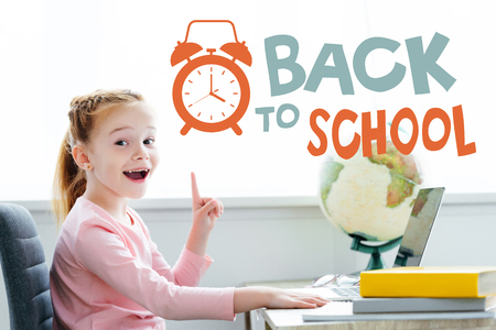 Cheerful redhead child pointing up with finger and smiling at camera while studying with books and laptop at home with back to school lettering with alarm clock