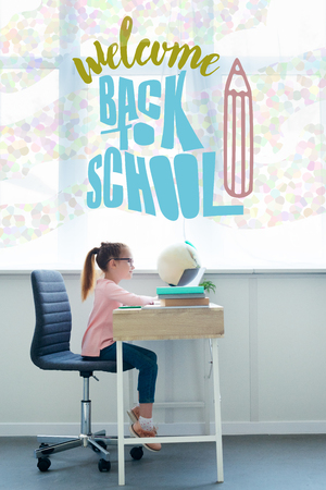 little schoolgirl studying with books and laptop at home with welcome back to school lettering and pencil illustration Stock Photo
