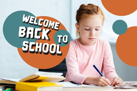 adorable red haired schoolgirl sitting at desk and studying at home with welcome back to school lettering