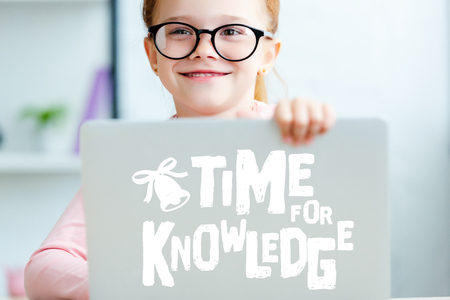 Adorable red haired schoolgirl in eyeglasses using laptop with time for knowledge lettering